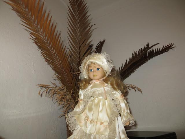 Fotografia macro de Boneca Antiga de Porcelana para criança em cima de guarda fato