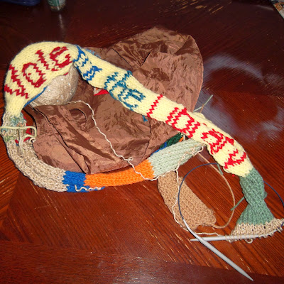 "Multicolored length of knitting on circular knitting needles, with phrase ""Vote For the Library"""