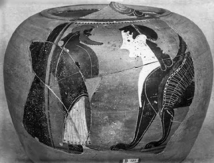 Ο γενειοφόρος Οιδίποδας, φορώντας μακρύ άσπρο χιτώνα και ιμάτιο, στέκεται μπροστά στη Σφίγγα. Μελανόμορφος αμφορέας με λαιμό από τις Κλαζομενές, περίπου 540-530 π.Χ. Βρέθηκε στο Tell Dafana στο Δέλτα του Νείλου. Λονδίνο, Βρετανικό Μουσείο, 1888,0208.101, B122 © Trustees of the British Museum