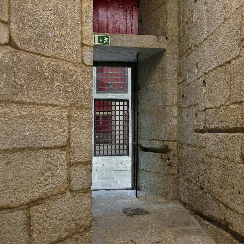 Passagem de uma sala para a outra em granito. Pela abertura vê-se as grades do outro lado