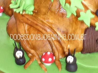 Bolo decorado Smurfs no formato de uma casinha tronco de árvore com cogumelos e formiguinhas decorando a casinha tronco de árvore.