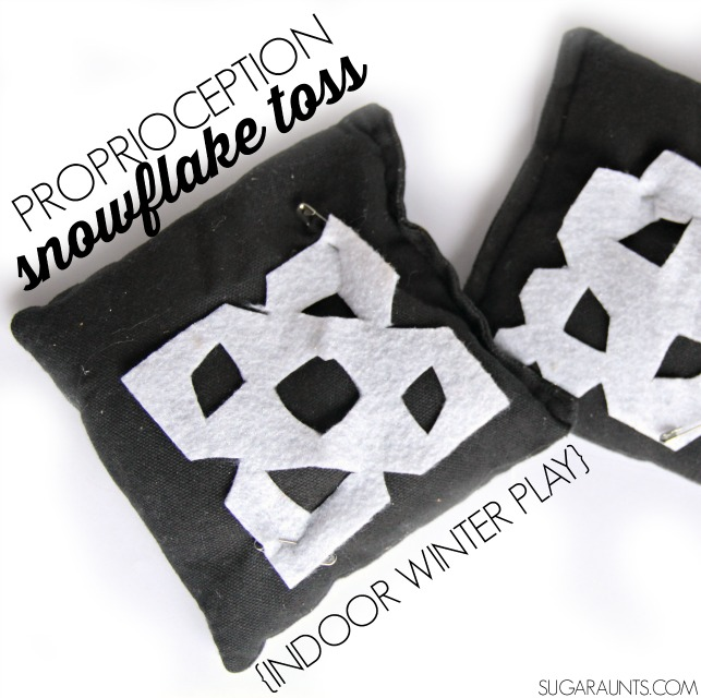 Proprioception indoor winter snowflake toss game for kids with bean bags. This is a great idea for days when it it too cold to go outside, or winter or snowflake themed party games.