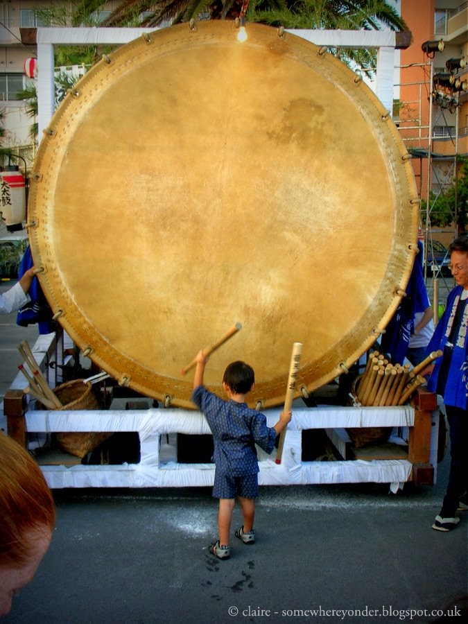 Small boy plays giant Taiko Drum at the Bentenjima Fireworks Festival, Japan