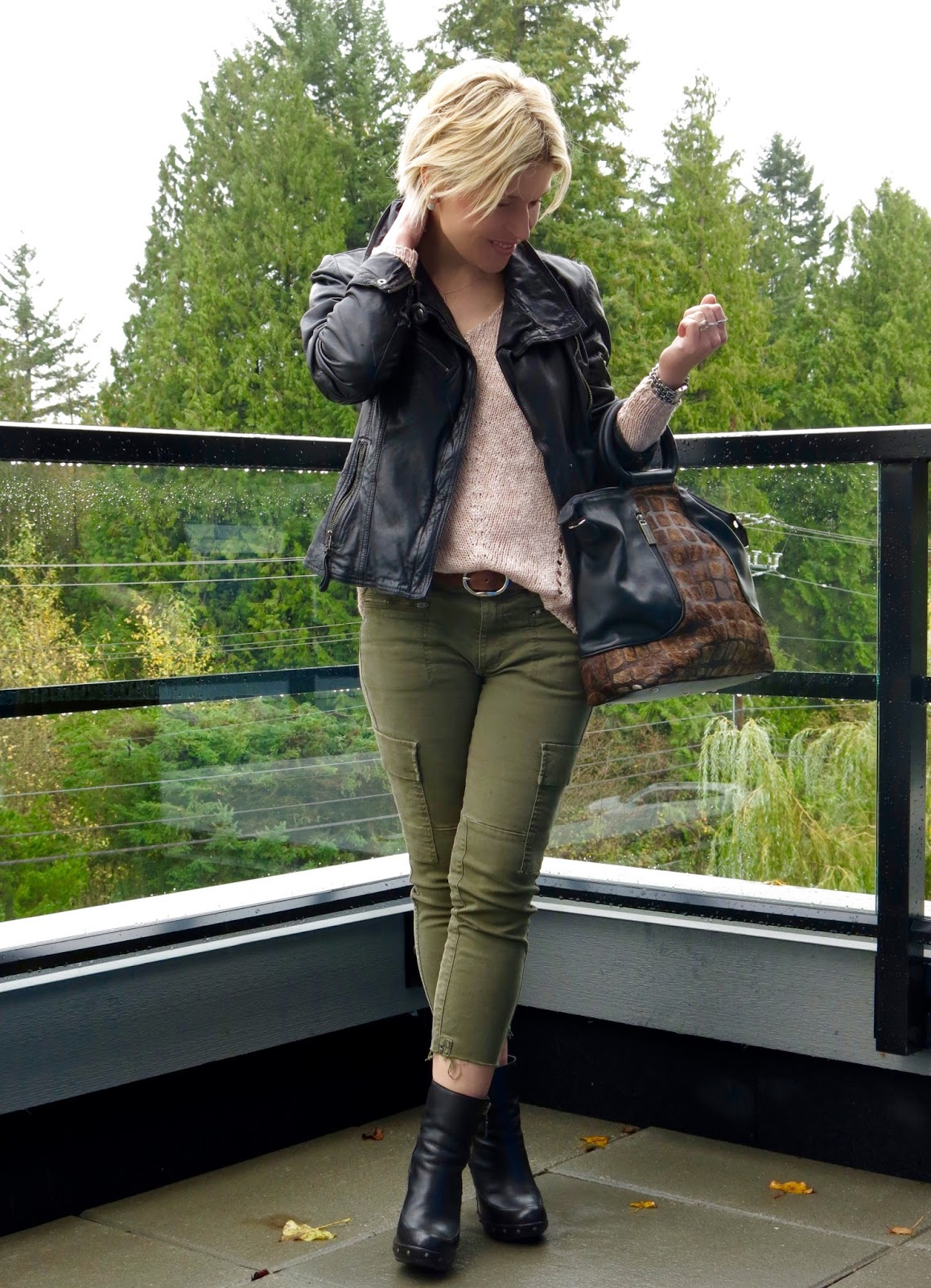styling skinny cargo pants with a drapey sweater, platform booties, and a moto jacket
