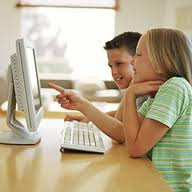 a little boy and girl sitting in front of a computer