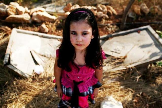 Menina palestina em frente a sua casa destruída