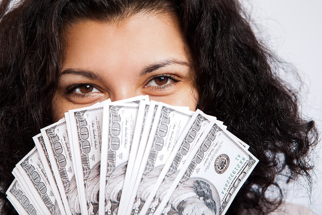 Girl holding fanned stack of money in front of her face