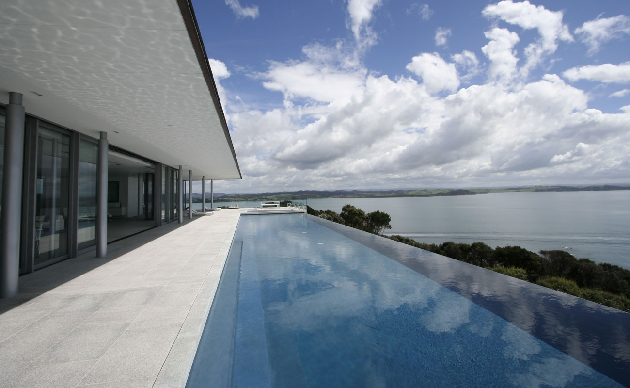 Infinity pool design at the edge of the sea in ibiza spain for Pool design nz