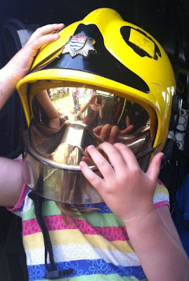 sitting in a fire truck wearing a helmet