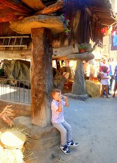 Niño tocando armónica sentado en pegollu de hórreo