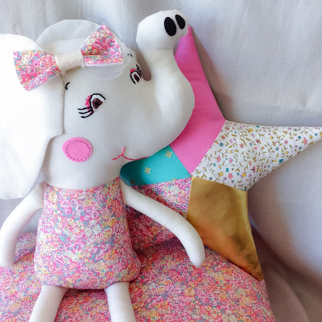 Elephant Doll sitting in front of Liberty Gold Star Cushion