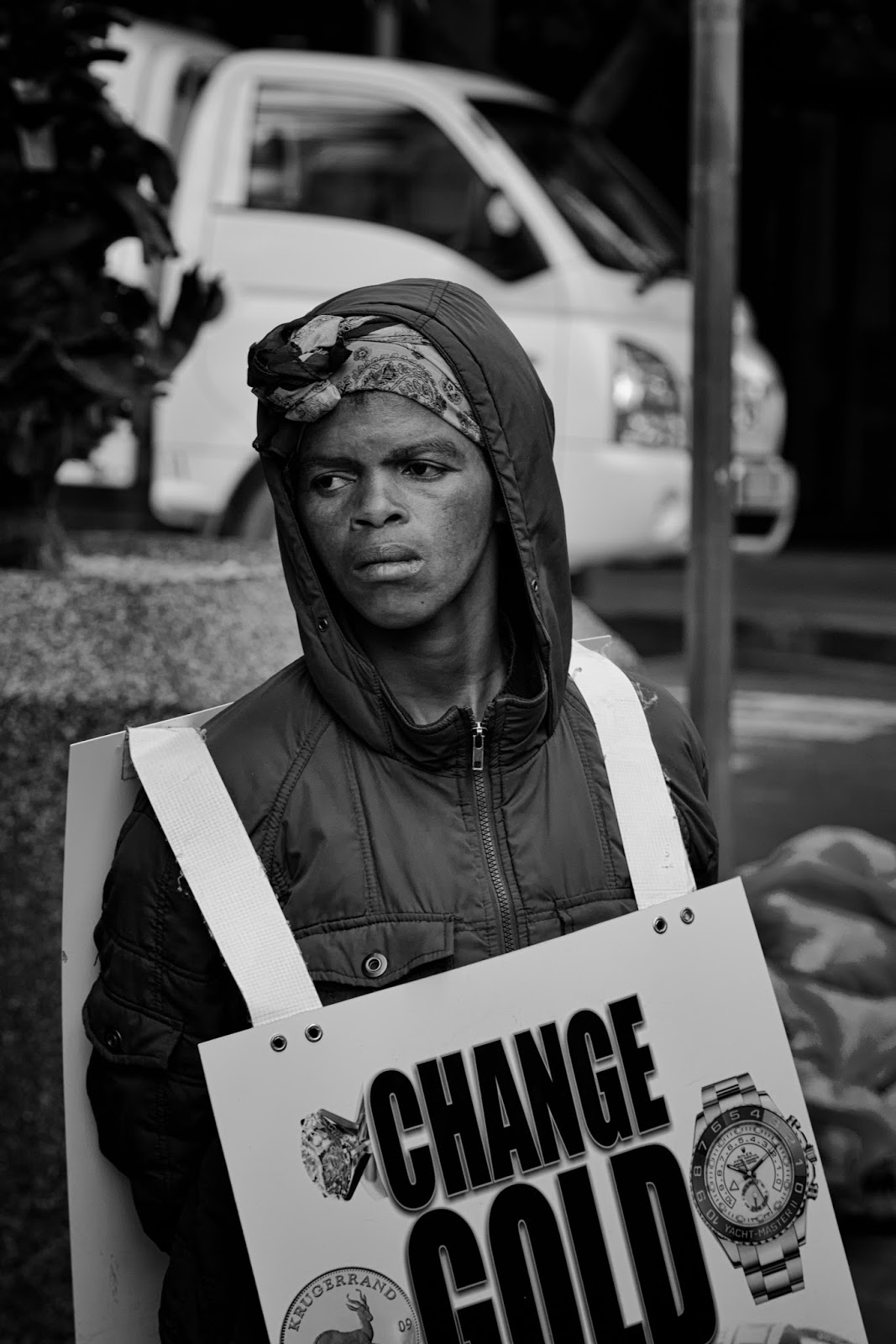 A street portrait of a human billboard holding a change gold sign