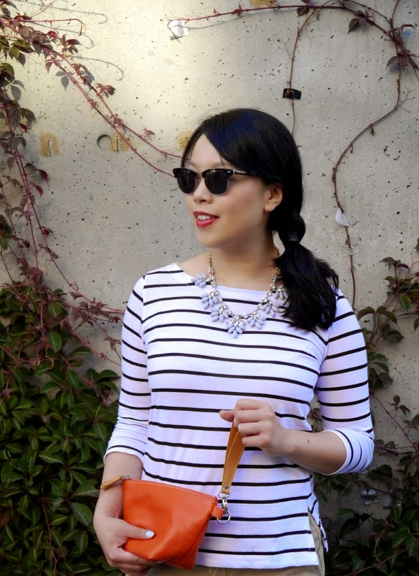 Benji Frank shades, black-and-white Breton stripes, grey and rhinestone statement necklace, orange wristlet