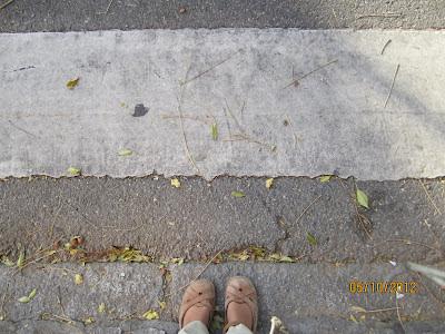 Se muestra el escaso contraste cromático existente en la zona de contacto del acerado con la calzada del paso de peatones. Se trata de una escala de grises en la que el gris del bordillo de la acera es algo más claro que el del asfalto.