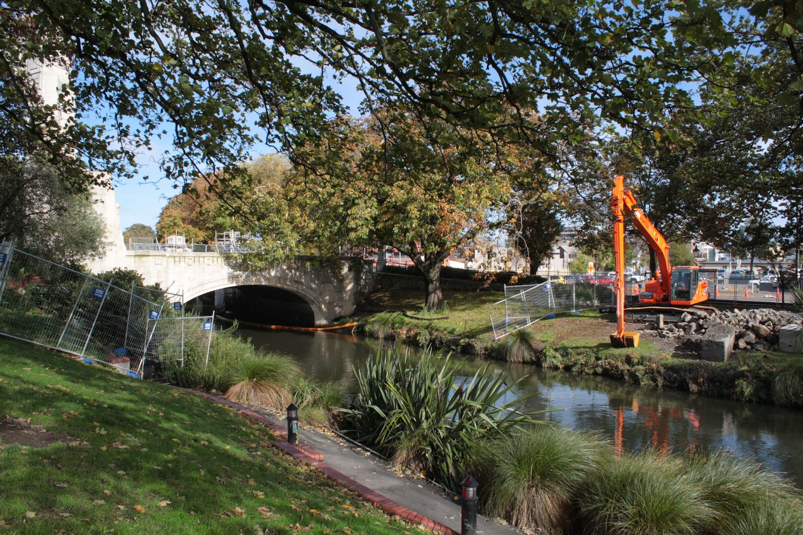 The Avon River, Christchurch, with diggers and hurricane fence.