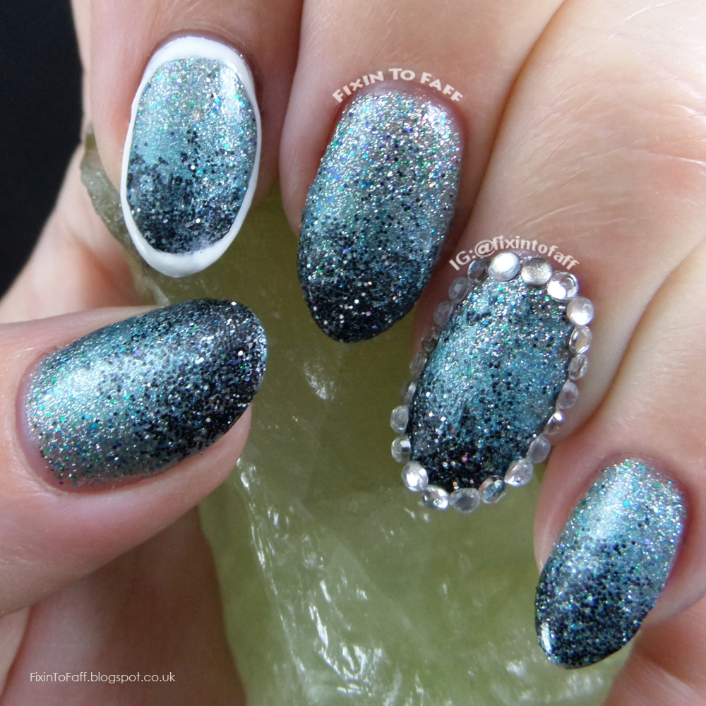 Loose glitter gradient nail art outlined with rhinestones and polish.