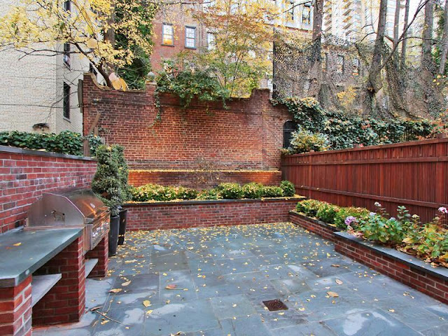 Ground level garden with brick walls, grill and built in planters with flowers