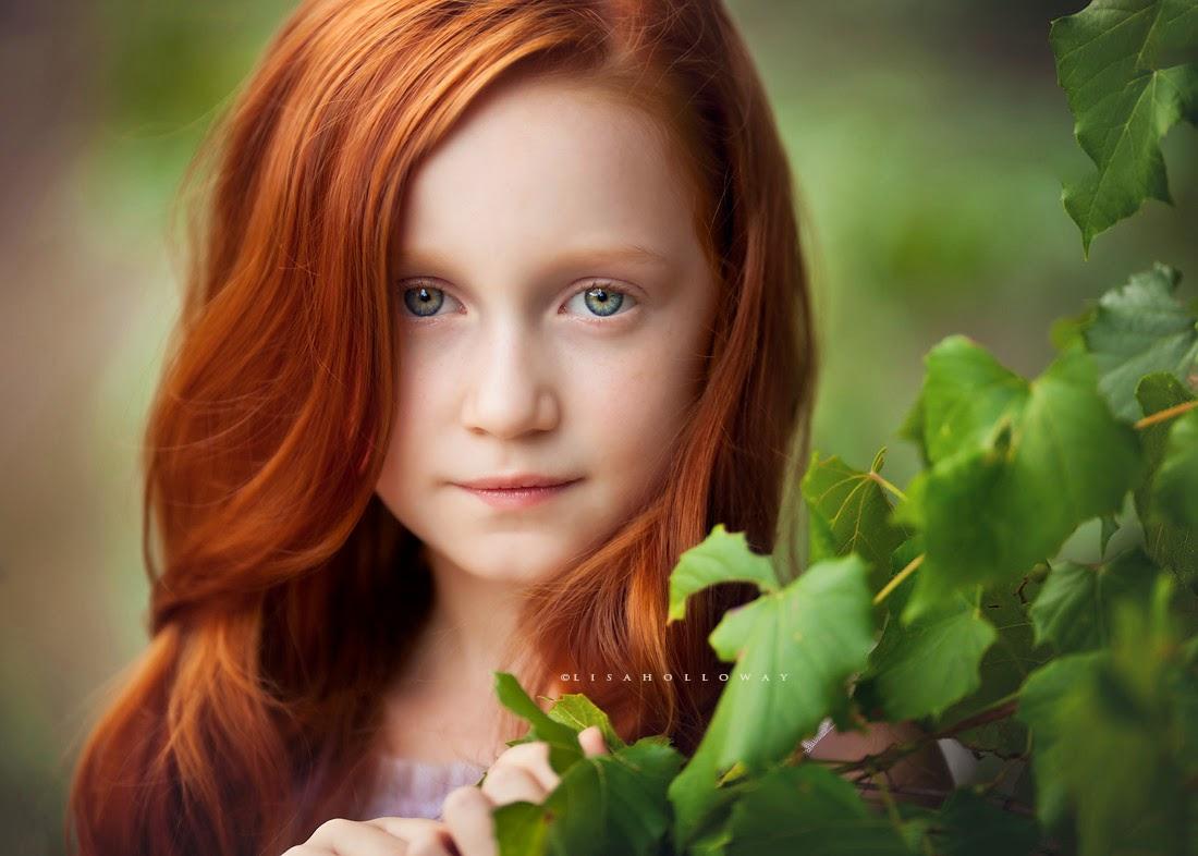 photo de Lisa Holloway représentant le portrait d'une jeune fille rousse derrière des feuilles d'arbre