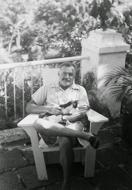 Hemingway with his cat, Boise, outside Finca Vigia.