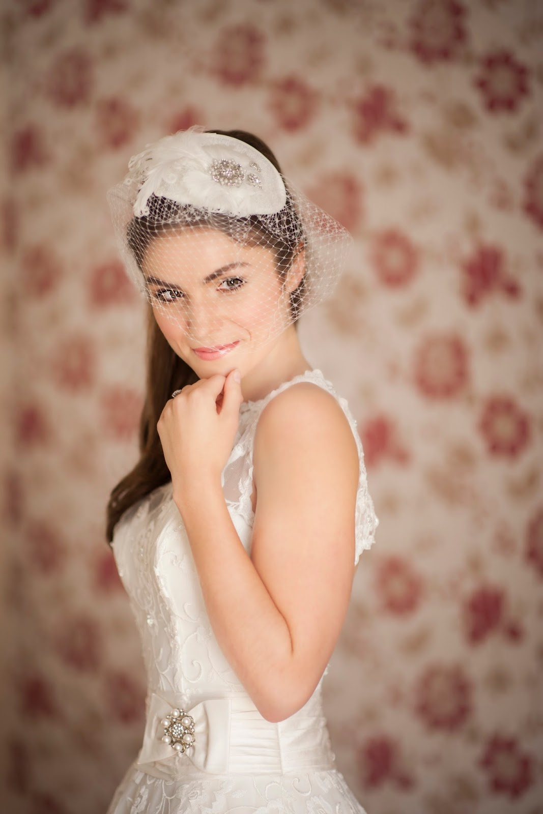 Model wears a fifties style gown and birdcage veil with a flirty ponytail hairstyle