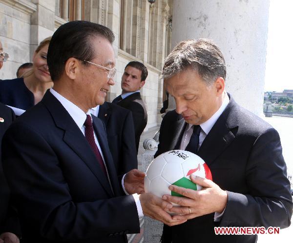 Premier Chin daje w darze pilke z wlasnym autografem premierowi Wegier