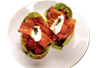 Jacket potatoes topped with tomato sauce, lettuce and bacon garnished with mayonnaise