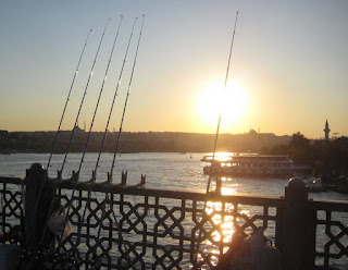 Fishing poles lined up along the Galata Bridge at sunset.