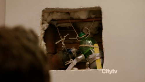 A convoluted and poorly designed collection of bottles, tape and string inside a hole int he wall, used to come to a very dodgy fix of plumbing (from the TV series New Girl)