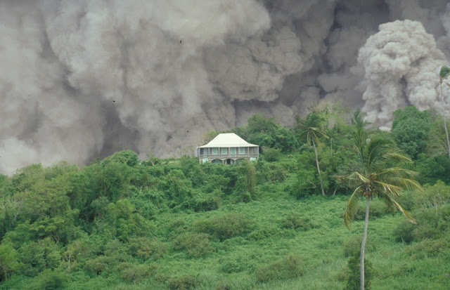 The Tar River Estate House on 17th September 1996 with a dome-collapse pyroclastic flow passing behind down the Tar River valley. This dome collapse continued for more than nine hours. A large part of the dome collapsed on 17th September and this caused a rapid reduction in pressure over the vent at the summit of the volcano. As a result, shortly before midnight, there was a magmatic explosion during which blocks of lava 1.5 m. in diameter were blasted 2.1 km. from the dome. The ongoing eruption of the Soufriere Hills Volcano has devastated much of the small Caribbean island of Montserrat. The eruption of the lava dome-building volcano began in 1995 and volcanic hazards have included pyroclastic flows, pyroclastic surges, vulcanian explosions, lateral blasts, ash clouds and lahars.
