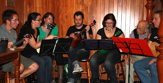 A group of people sitting behind music stands, holding ukuleles, discussing something animatedly.
