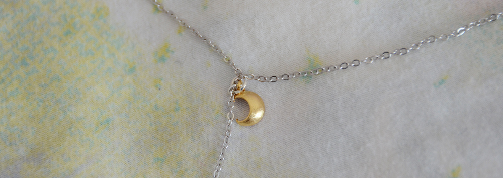 Close-up of the golden crescent moon charm on the Moon Princess necklace from TeaCupCastle.