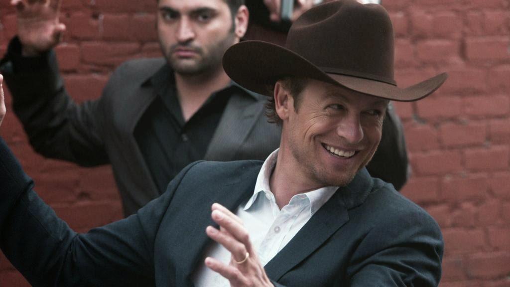 Patrick Jane, cu pălărie de cowboy pe cap, este amenințat cu o armă automată de liderii unei rețele de trafic de organe și carne vie