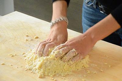 Crostata di mele: spostare l'impasto sulla spianatoia e compattarlo con le mani