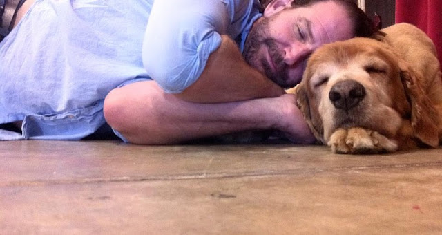 man in blue shirt lying on the floor with his head on a sleeping golden retriever