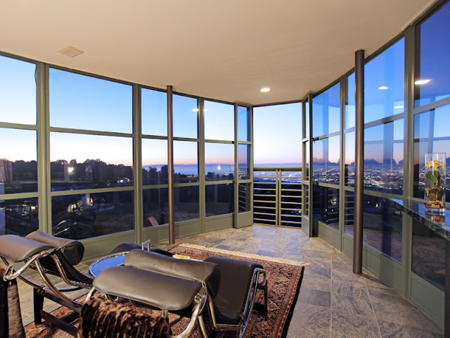 Photo of the room with two leather chairs and glass walls to provide incredible views