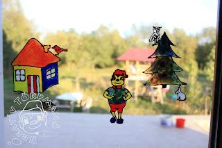 Szöveg: Ablakmese részlet. Kép: Közelkép az ablakról ahova felkerült az előre megrajzolt Törpmanó házikója, rajta egy piros madár, mellette jobbra Törpmanó kirándulásra készen. Tőle jobbra egy fenyőfa, amin bagoly ül, alatta mege egy nyuszi. Minden figura a játszófüzetből volt átmásolva üvegfestékkel.