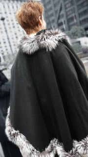 Cape with fur trimmed edges.