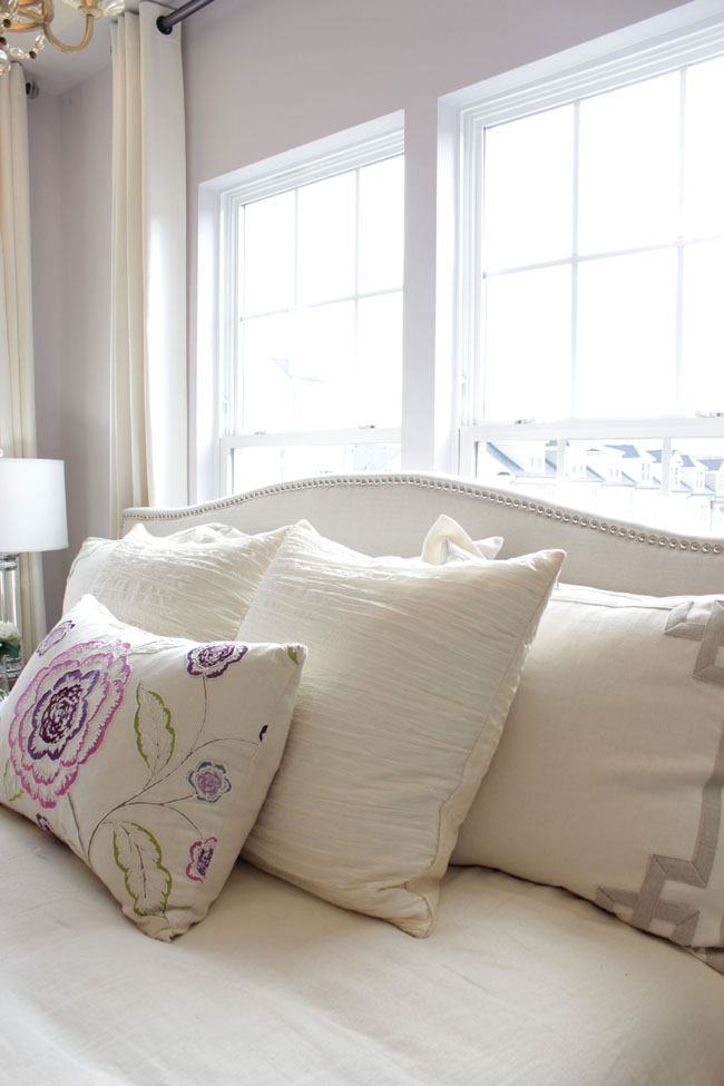 A nail-head row all around a padded headboard creates coziness in the bedroom