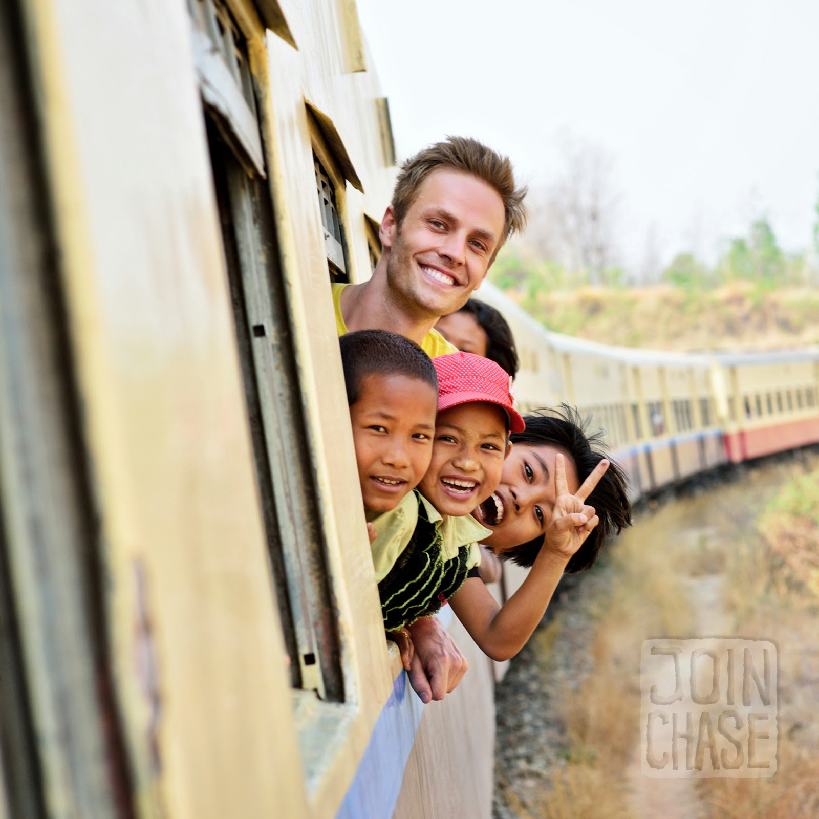 Chase Chisholm peeking out the window with children on a train from Yangon to Bagan, Myanmar.