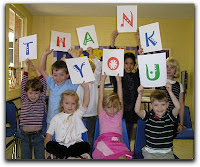 children hold thank you sign