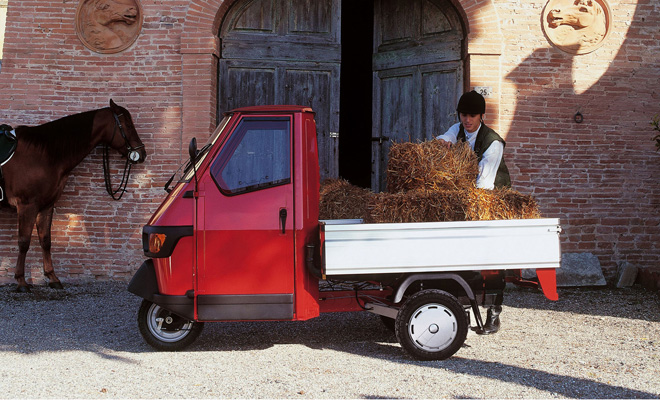 Piaggio Ape pickup carrying bales of hay