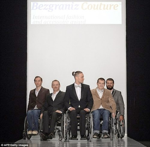 Five men in wheelchairs in a fashion show pose, each wearing a different style of fashionable suit