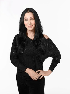 Cher standing in a black dress