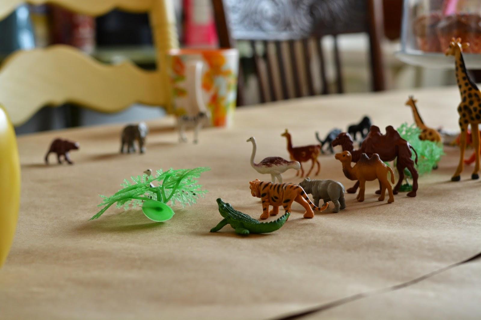 plastic zoo animals on table.