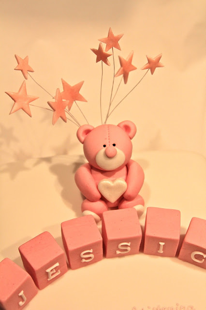 Cute pink teddy bear cake decoration with stars