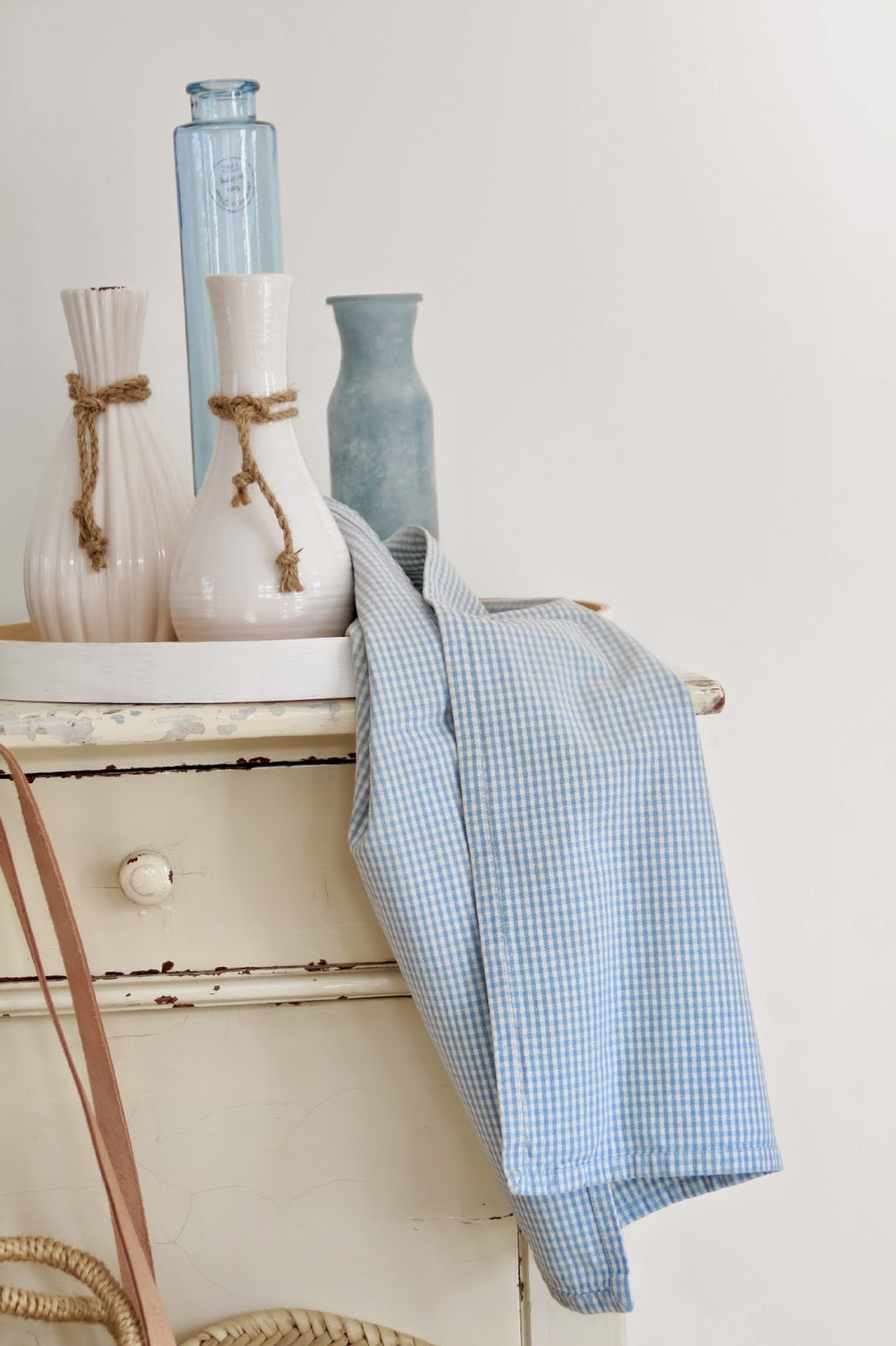Vasen in weiß und hellblau auf Kommode mit hellblau kariertem Geschirrtuch im Vordergrund