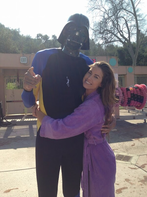Kareem Abdul-Jabbar in a Darth Vader mask gets a hug from a bathrobe-wearing Katherine Webb.