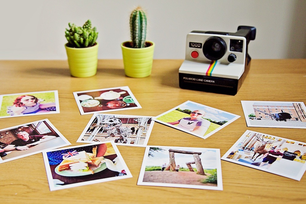 Polaroid land camera with Sticky9 print box with Instagram prints and cacti decoration.