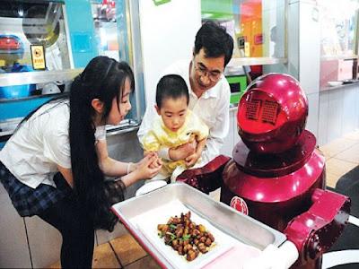 KANAK-KANAK ini terpegun melihat pelayan robot membawa makanan.