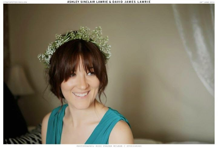 bridesmaid wears her hair in a soft vintage roll with a babys breath floral crown
